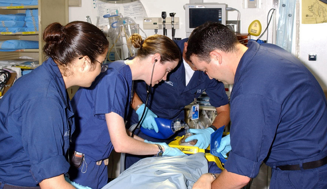 Physician leading a trauma team of nurses and EMTs