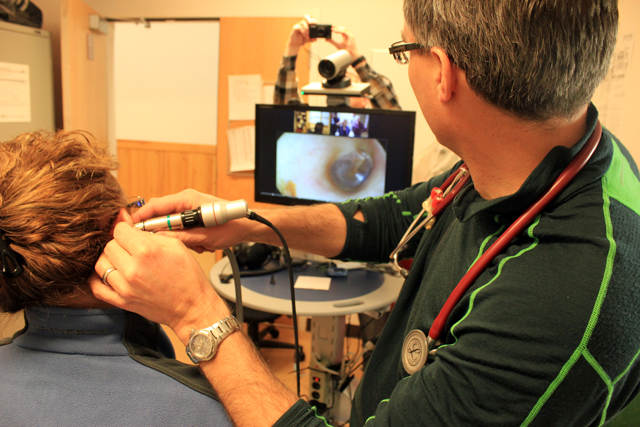 Dr. John Pawlovich using a telehealth-enabled ENT camera to examine a patient during a videoconferenced appointment in the remote community of Takla Landing
